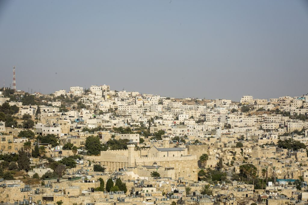 "View of Hebron from The Centre for Youth Against Settlements in Hebron, 13 September, 2017. The center is based in an old Palestinian house that used to be an Israeli military base, once the soldiers left the settlers tried to take it, occupying it several times. The YAS group decided to fight and resist the occupation, and after several direct actions and legal challenges the Israeli court finally recognised the building as a legitimate Palestinian property. Issa Amro and Farid al-Atrash want an end to Israeli settlements – a war crime stemming from Israel's 50-year occupation of Palestinian land. Israel has made many parts of the occupied territories no-go zones for Palestinians, making it impossible for them to move about freely. By contrast, Jewish Israeli settlers are free to go where they wish.  Dedicated to non-violence, Issa and Farid brave constant threats and attacks by Israeli soldiers and settlers. Issa encourages Palestinian youths to find non-violent ways to oppose Israel's occupation and discriminatory laws in Hebron. For this, Israeli forces have arrested him more than once. They have beaten, blindfolded, and interrogated him. ""The Israeli occupation forces target us to silence us,"" says Issa. Farid, a lawyer who exposes abuses by the Palestinian and Israeli authorities, faces similar harassment.  In February 2016, Issa and Farid joined a peaceful protest in the city of Hebron marking 22 years since Israel first closed one of its streets, al-Shuhada, to Palestinians. Hebron's 200,000 Palestinians are effectively held hostage by the 800 Israeli settlers who live in its centre. The men now face ludicrous charges clearly designed to obstruct their human rights work."