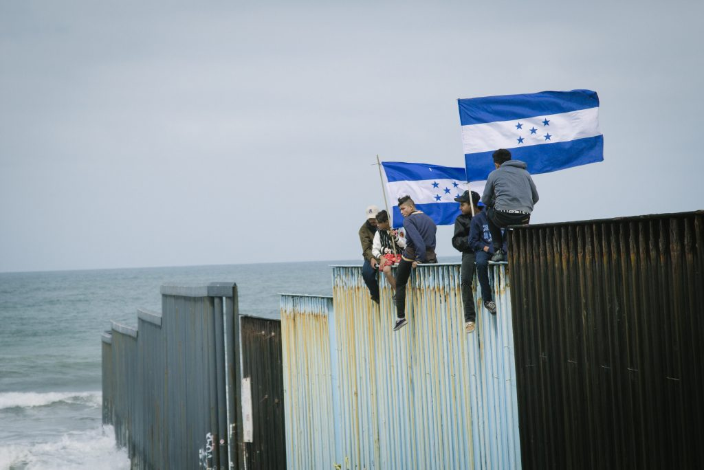 Billboard and migrant caravan in Tijuana