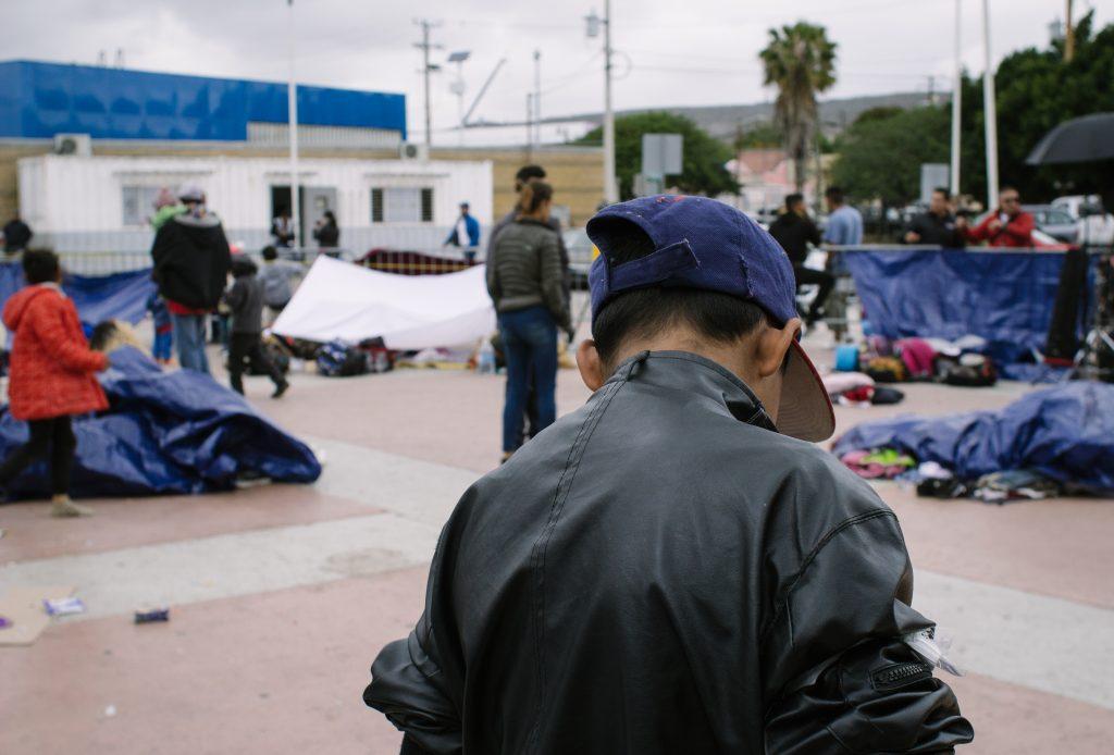 Billboard and migrant caravan in Tijuana